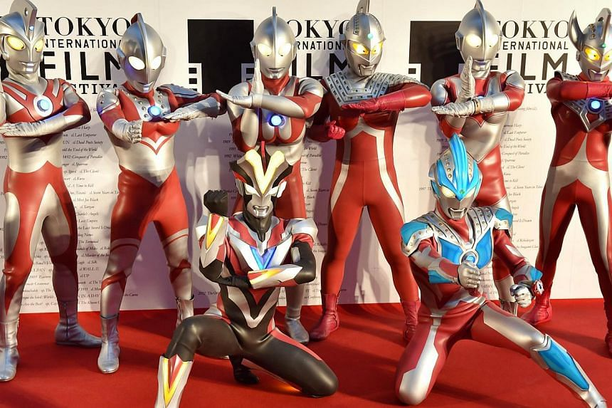 Actors clad in body suits of Ultrman series characters pose on the red carpet for the 27th Tokyo International Film Festival opening ceremony in Tokyo on Oct 23, 2014. -- PHOTO: AFP