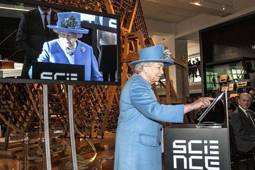 Britain's Queen Elizabeth presses a button to send her first Tweet during a visit to the 'Information Age' Exhibition at the Science Museum, in London on Oct 24, 2014. -- PHOTO: AFP
