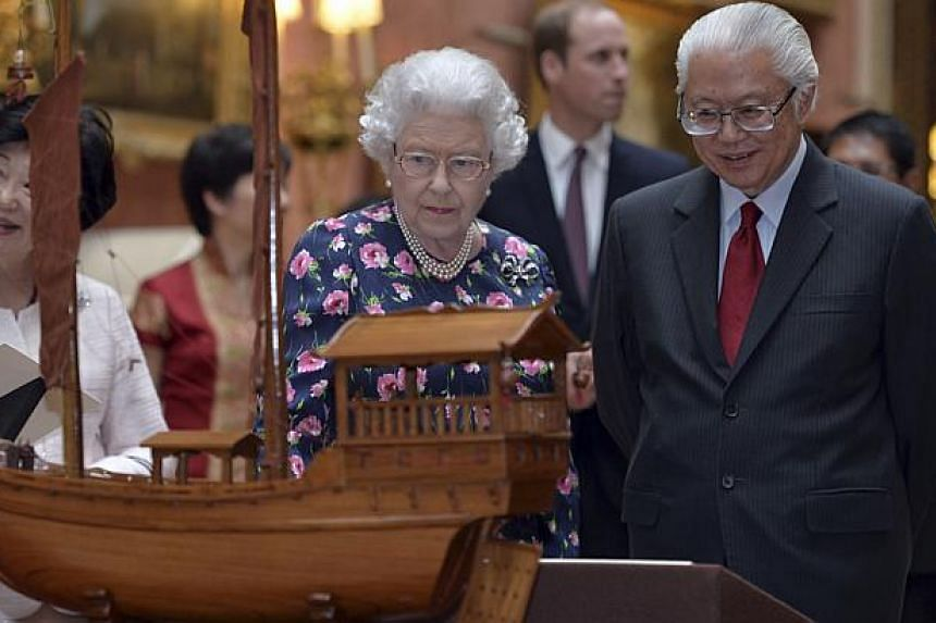 Britain's Queen Elizabeth II and President Tony Tan Keng Yam view a display of Singaporean items from the Royal Collection at Buckingham Palace in London on Oct 21, 2014. -- PHOTO: REUTERS