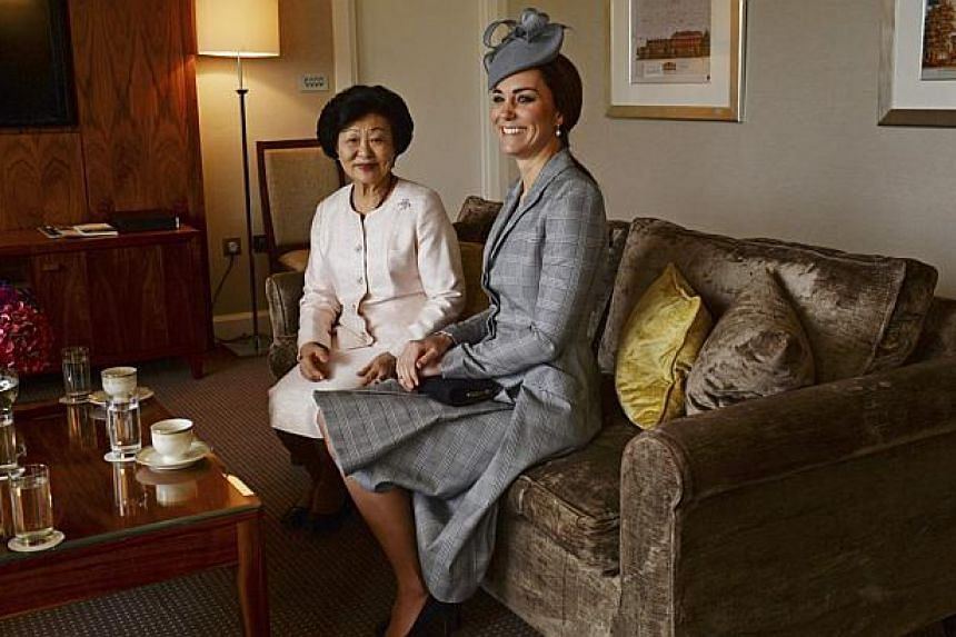 Britain's Catherine, Duchess of Cambridge (right) sits with Mrs Mary Tan, the wife of President Tony Tan Keng Yam, at the Royal Garden Hotel in London on Oct 21, 2014. -- PHOTO: REUTERS
