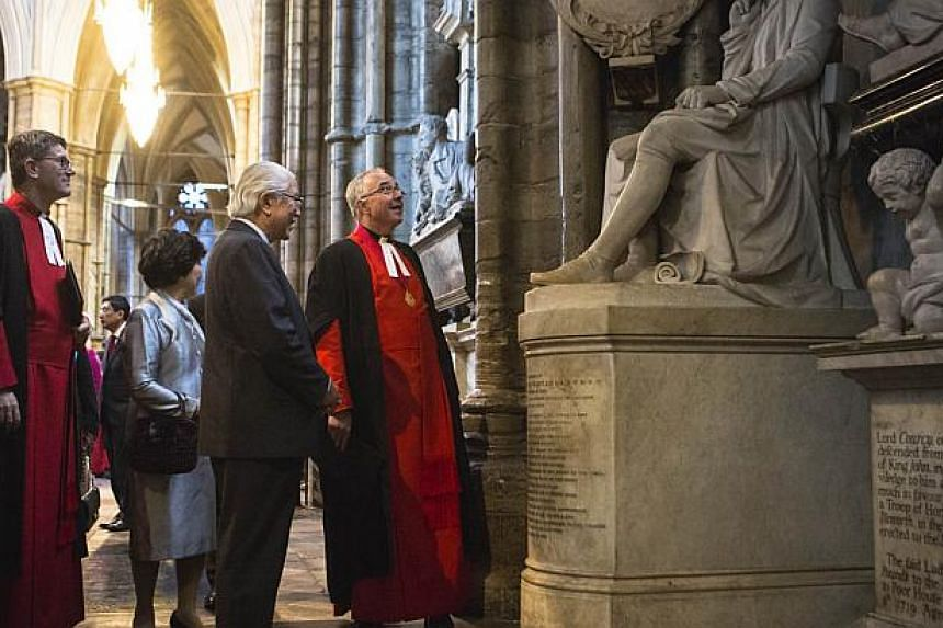 President Tony Tan Keng Yam and his wife Mary are shown the statue of Sir Thomas Stamford Raffles by Reverend Dr John Hall, Dean of Westminster (right) in Westminster Abbey on Oct 21, 2014. -- PHOTO: AFP