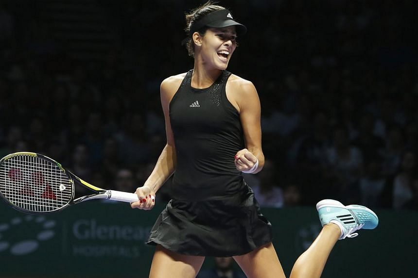 Ana Ivanovic of Serbia celebrates a point against Simona Halep of Romania during their WTA Finals singles tennis match at the Singapore Indoor Stadium on Oct 24, 2014. -- PHOTO: REUTERS