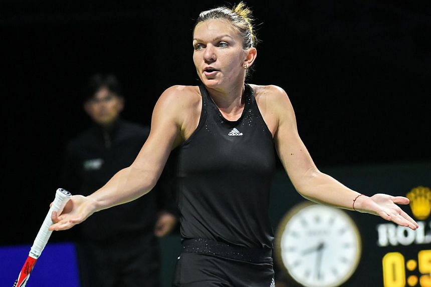 Simona Halep of Romania reacts during a match against Ana Ivanovic of Serbia at the Women's Tennis Association (WTA) finals round robin match in Singapore on Oct 24, 2014. -- PHOTO: AFP