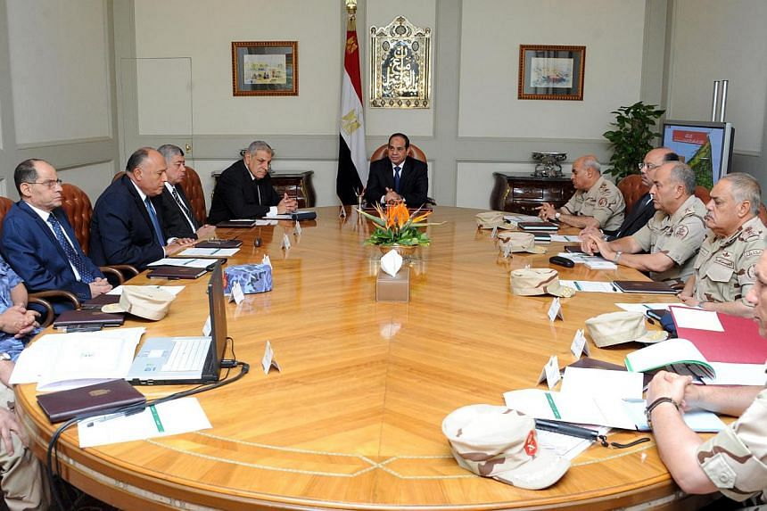 Egypt's President Abdel Fattah al-Sisi (centre) chairs a meeting with the National Defence Council in Sheikh Zuweid, North Sinai on Oct 24, 2014. A car bomb in Egypt's Sinai Peninsula killed at least 28 soldiers, in one of the deadliest attacks on se