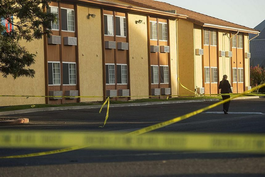 Crime scene tape criss-cross a Motel 6 parking lot where Sheriff's Deputy Danny Oliver was killed in Sacramento, California on Oct 24, 2014. -- PHOTO: REUTERS