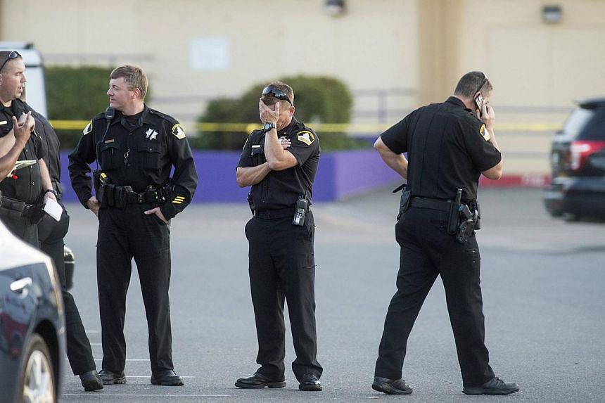 Sacramento County Sheriff Lieutenant Palmer covers his face while gathered with fellow officers near a Motel 6 parking lot where Sheriff's Deputy Danny Oliver was killed in Sacramento, California on Oct 24, 2014.