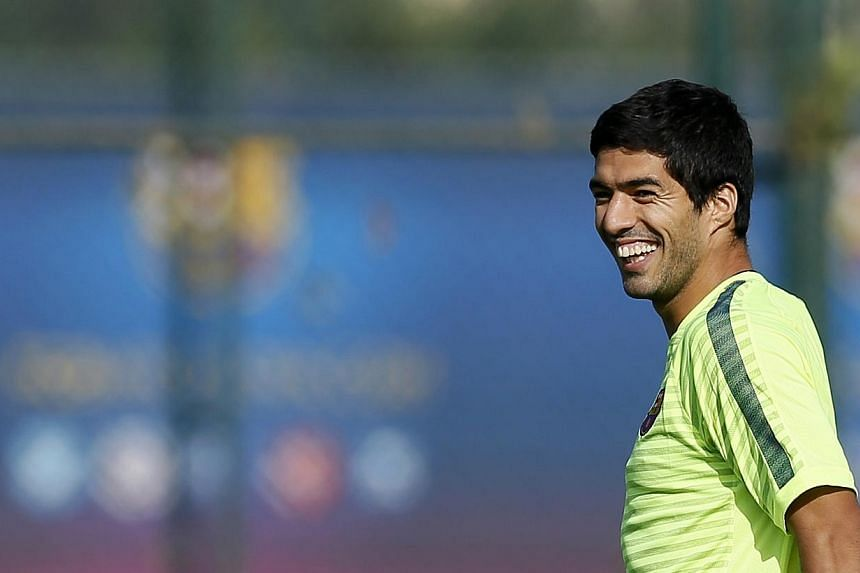 Barcelona's players Luis Suarez smiles during a training session at Joan Gamper training camp, near Barcelona on Oct 20, 2014. -- PHOTO: REUTERS