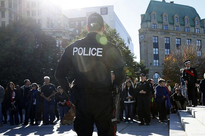 Police officers attend a ceremony returning sentries to the Tomb of the Unknown Soldier at the National War Memorial in Ottawa on Oct 24, 2014. -- PHOTO: REUTERS