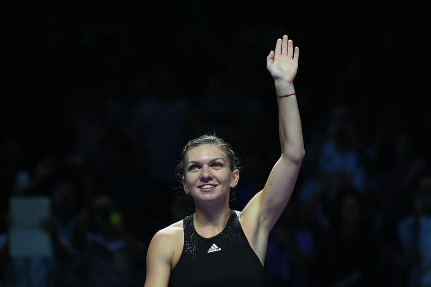 Simona Halep of Romania waves to supporters after defeating Agnieszka Radwanska of Poland during the semi finals of the Women's Tennis Association (WTA) finals in Singapore on Oct 25, 2014. -- PHOTO: AFP