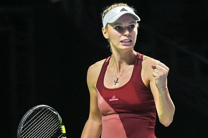 Caroline Wozniacki reacts to a point againstSerena Williams during the semi-finals of the WTA Finals in Singapore on Oct 25, 2014. -- PHOTO: AFP