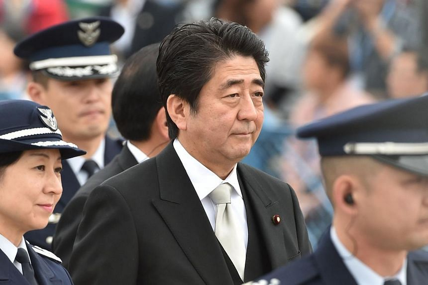 Japanese Prime Minister Shinzo Abe (centre) arrives at a review ceremony at the Japan Air Self-Defense Force's Hyakuri air base at Omitama in Ibaraki prefecture on Oct 26, 2014. -- PHOTO: AFP
