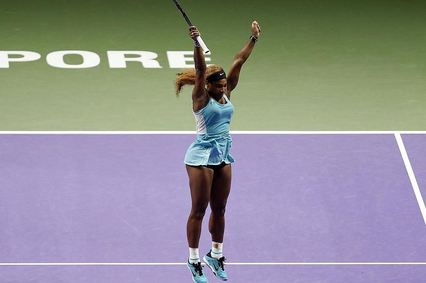 Serena Williams of the US celebrates defeating Simona Halep of Romania in the women's singles final tennis match of the WTA Finals at the Singapore Indoor Stadium on Oct 26, 2014. -- PHOTO: REUTERS