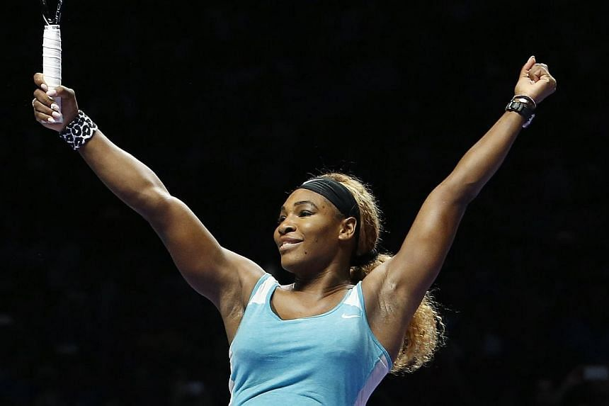 Serena Williams of the United States celebrates defeating Simona Halep of Romania in the women's singles final tennis match of the WTA Finals at the Singapore Indoor Stadium on Oct 26, 2014. -- PHOTO: REUTERS