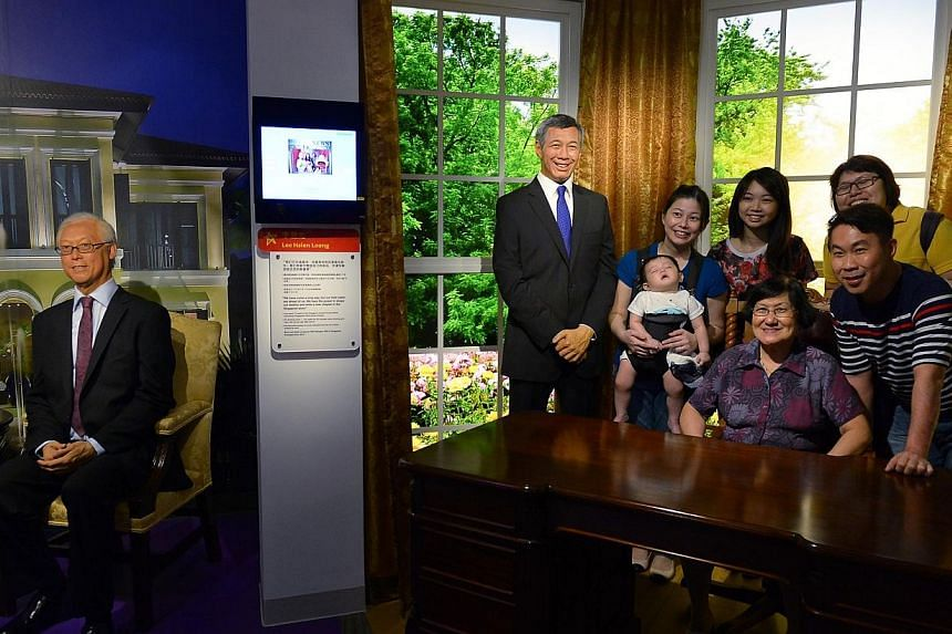 Visitors to Madame Tussauds Singapore pose for a photo with Prime Minister Lee Hsien Loong. The wax figurine of Emeritus Senior Minister Goh Chok Tong is seen on the left. -- ST PHOTO: NG SOR LUAN