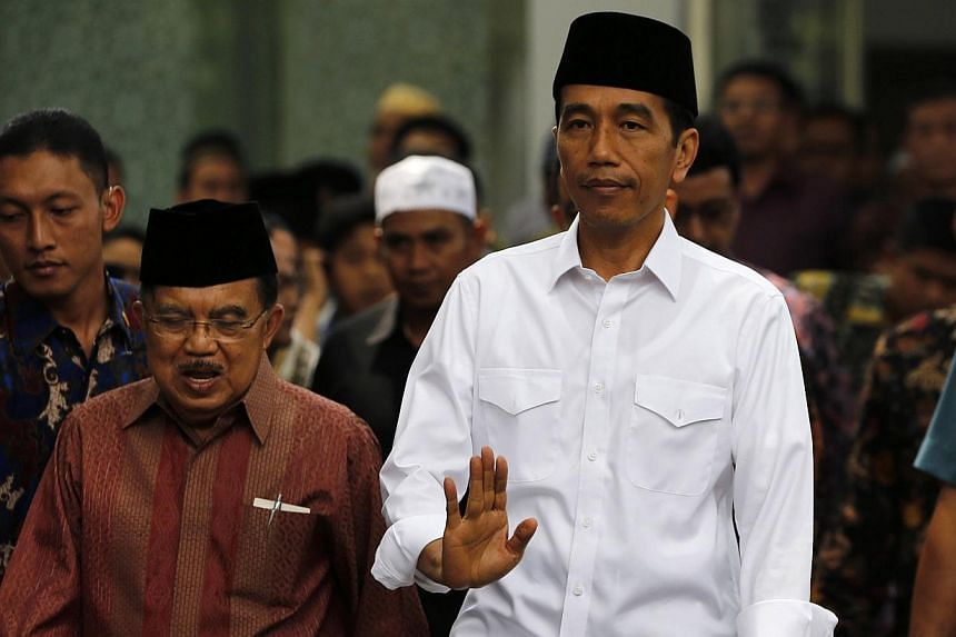 Indonesia's President Joko Widodo (right) waves as he walks with vice president Yusuf Kalla after Friday prayers at the Presidential palace in Jakarta, on Oct 24, 2014. -- PHOTO: REUTERS