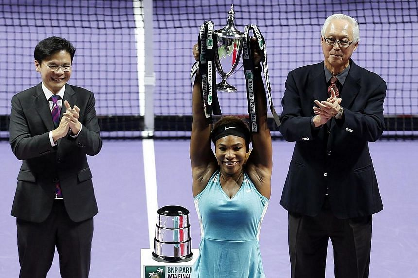 Serena Williams of the US poses with the trophy after defeating Simona Halep of Romania in the women's singles final tennis match of the WTA Finals at the Singapore Indoor Stadium on Oct 26, 2014. -- PHOTO: REUTERS
