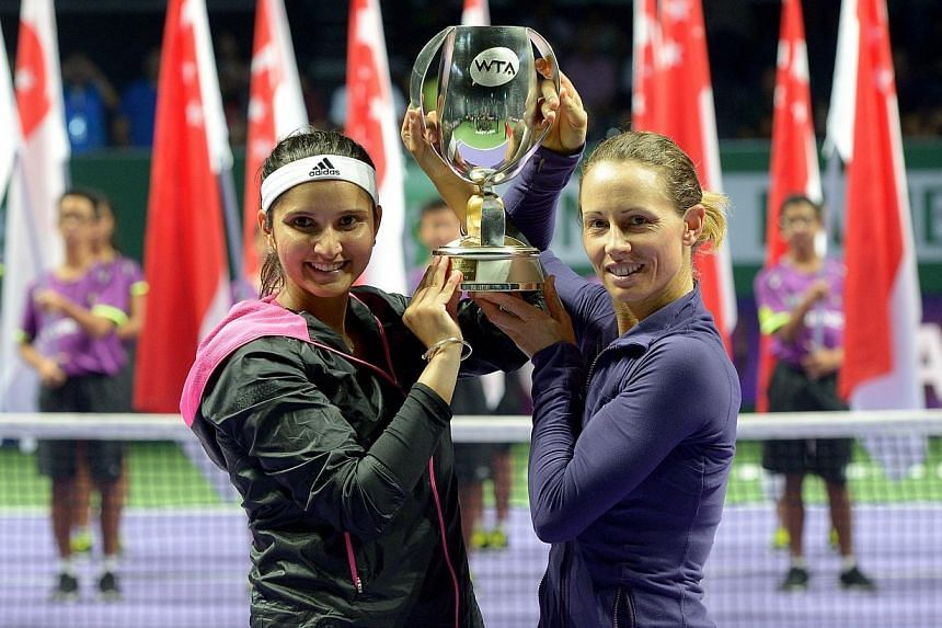 The pair of Zimbabwean Cara Black (right) and India's Sania Mirza won the BNP Paribas WTA Finals Singapore doubles title on Sunday afternoon in emphatic style, thrashing defending champions Peng Shuai and Hsieh Su-wei 6-1, 6-0 to lift the trophy. --