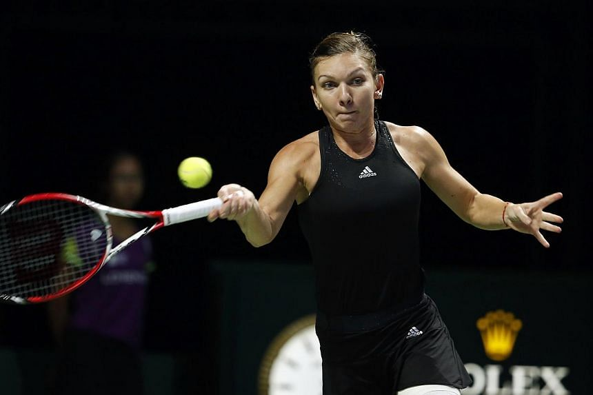 Simona Halep of Romania hits a return to Serena Williams of the US during their women's singles final tennis match of the WTA Finals at the Singapore Indoor Stadium on Oct 26, 2014. -- PHOTO: REUTERS