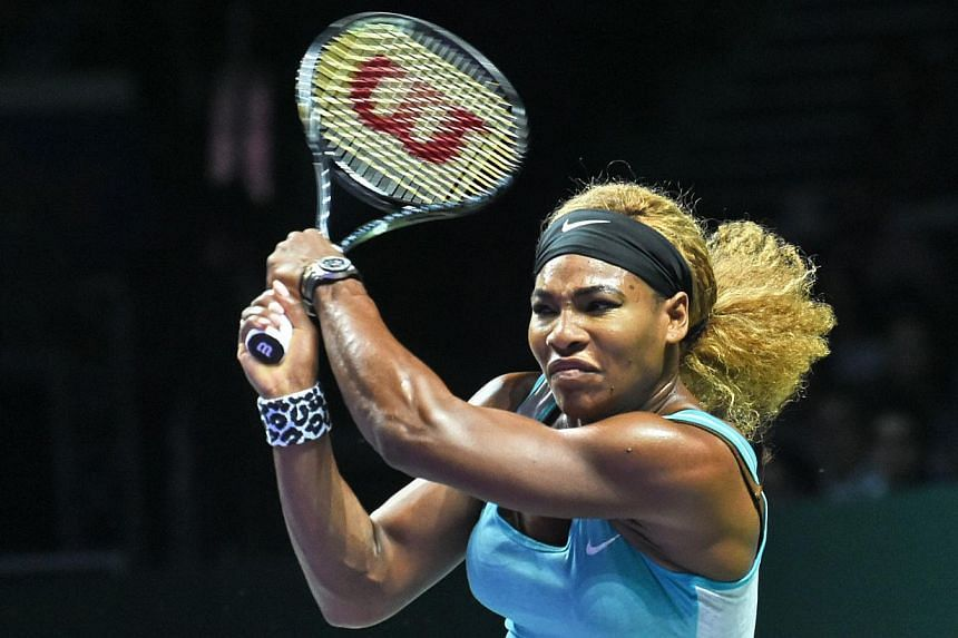 Serena Williams of the US plays a shot against Simona Halep of Romania during the finals of the Women's Tennis Association (WTA) finals in Singapore on Oct 26, 2014. -- PHOTO: AFP