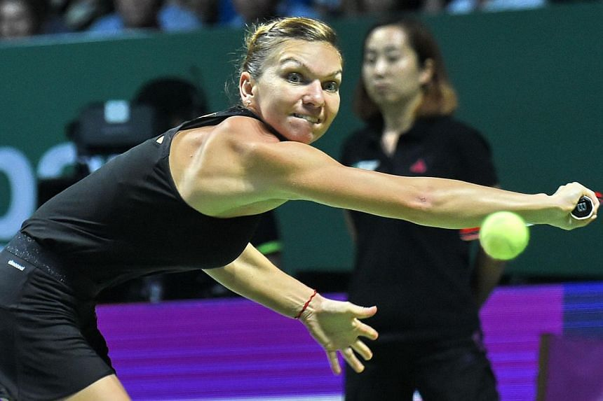 Simona Halep of Romania plays a shot against Serena Williams of the US during the finals of the Women's Tennis Association (WTA) finals in Singapore on Oct 26, 2014. -- PHOTO: AFP