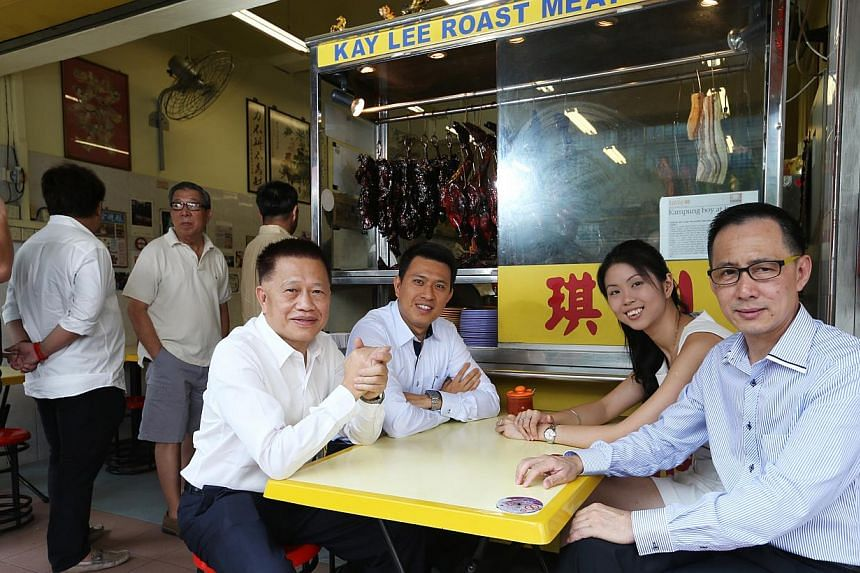 Mr Michael Mun (seated, right), Aztech Group's chairman, with (second from right) his eldest son Jeremy, food scientist Christine Lee and operations manager Sam Ng. -- ST PHOTO: SEAH KWANG PENG