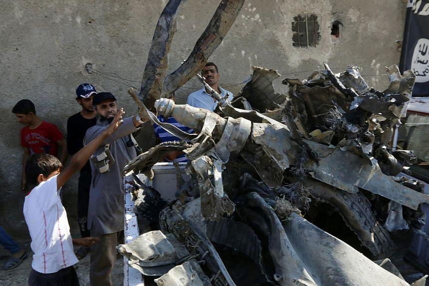 People load parts of the wreckage of a Syrian war plane onto a truck after it crashed in Raqqa, in northeast Syria, after being shot down by anti-aircraft guns on Sept 16, 2014.Germany's intelligence service believes fighters of the Islamic Sta