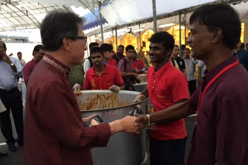 Labour chief Lim Swee Say (left), who is also Minister in the Prime Minister's Office, speaking with migrant workers at a Deepavali feast at Sri Srinivasa Perumal Temple along Serangoon Road on Sunday. Mr Lim also helped distribute food to the 5,000