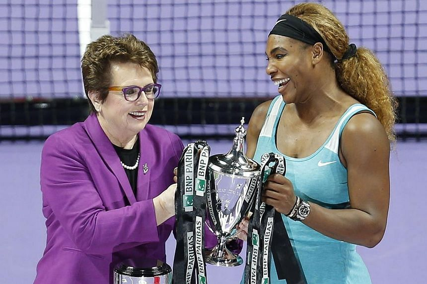 Tennis legend Billie Jean King presents Serena Williams of the US with the trophy after Williams defeated Simona Halep of Romania in the women's singles final tennis match of the WTA Finals at the Singapore Indoor Stadium on Oct 26, 2014. -- PHOTO: R
