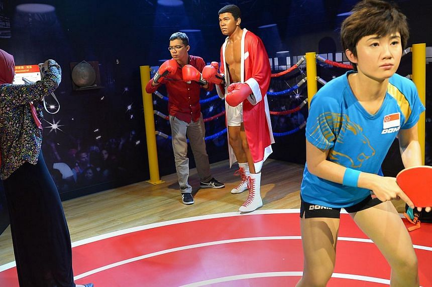 Ahmad Fadzil, 21, poses for a photograph with a wax figurine of famed boxer, Muhammad Ali. The wax figurine of table tennis player, Feng Tianwei, is on right. -- ST PHOTO:NG SOR LUAN