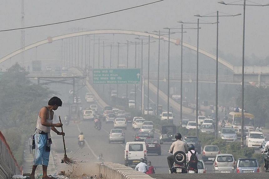 An Indian sweeper cleans a flyover as smog covers the capital's skyline the morning after celebrations for the Diwali festival in New Delhi on Oct 24, 2014. -- PHOTO: AFP