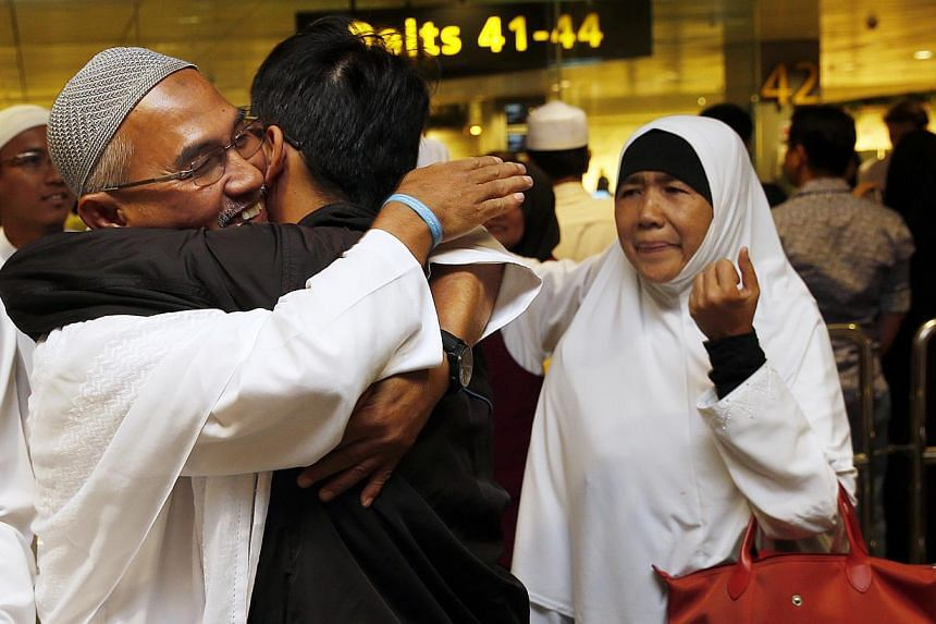 Mr Jamallvdin A. Latiff (left), 60, and his wife Fatiman Mohan (left), 59, together with their son Mohd Suffian, 30, at Changi Airport Terminal 3. -- ST PHOTO:LAU FOOK KONG