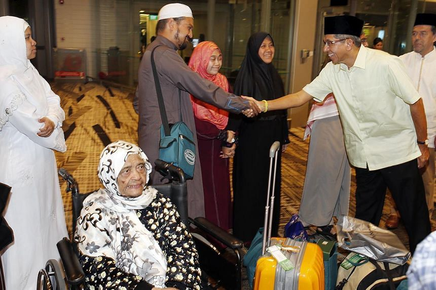 About 120 pilgrims returning from their haj journeys in Saudi Arabia were greeted by Minister-in-charge of Muslim Affairs Yaacob Ibrahim after they touched down at Changi Airport on Sunday morning. -- ST PHOTO:LAU FOOK KONG