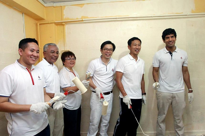 Sembawang GRC's (from left) Amrin Amin, Hawazi Daipi, Ellen Lee, Ong Teng Koon, Ong Ye Kung and Vikram Nair pose for a photo in a flat they helped clean and paint.-- PHOTO: LIANHAEZAOBAO