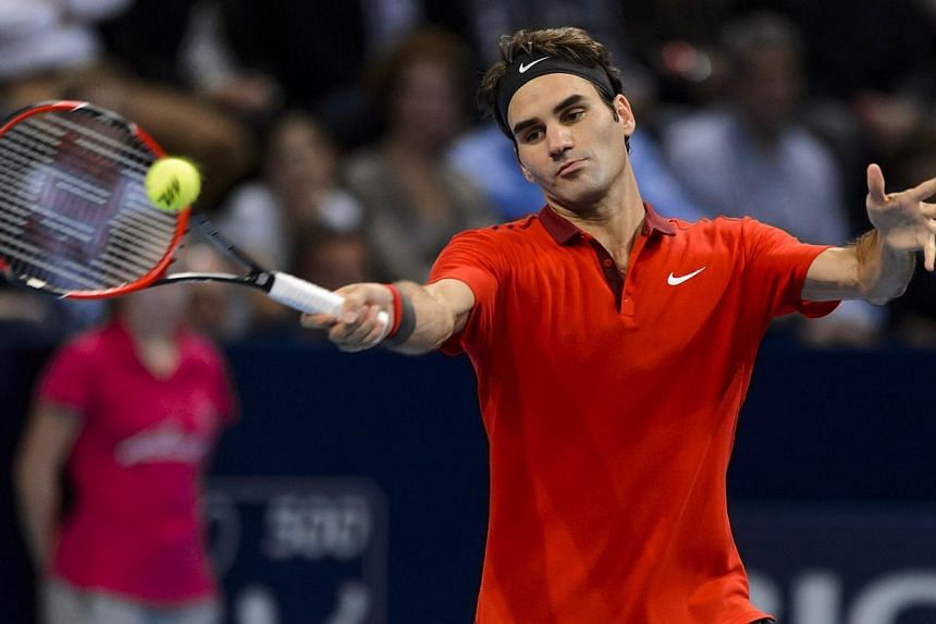 Roger Federer of Switzerland returns a ball during his semi final match against Ivo Karlovic of Croatia at the Swiss Indoors ATP 500 tennis tournament in Basel on Oct 25, 2014. -- PHOTO: AFP