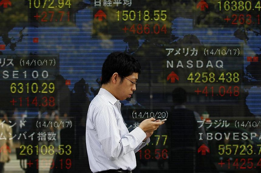 A pedestrian uses his mobile phone as he walks past an electronic board showing the stock market indices of various countries outside a brokerage in Tokyo on Oct 20, 2014. -- PHOTO: REUTERS
