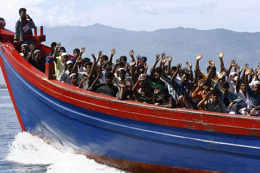 Ethnic Rohingya refugees from Myanmar wave as they are transported by a wooden boat to a temporary shelter in Krueng Raya in Aceh Besar in this April 8, 2013 file photo.A climate of fear in Myanmar's Rakhine state is pushing stateless Rohingya