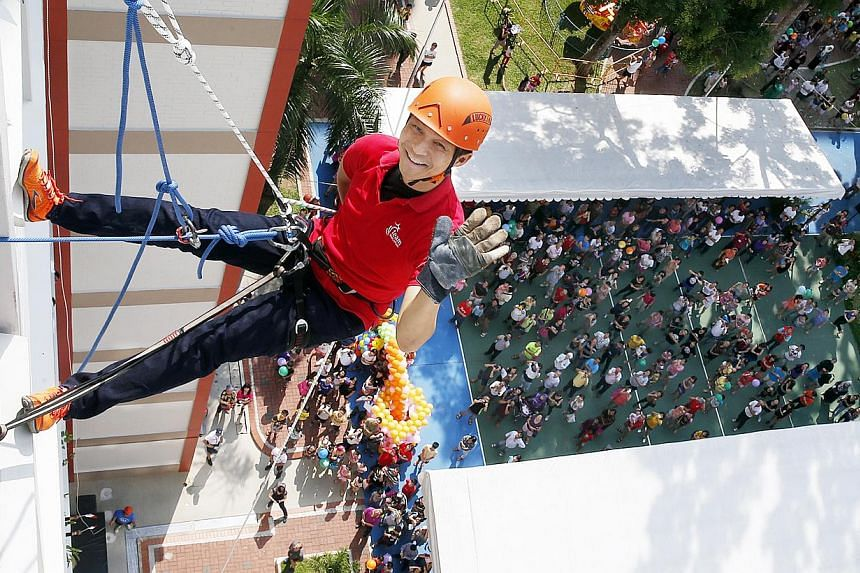 """Mr Tan Chuan-Jin at a family carnival in Chua Chu Kang yesterday, where he abseiled 11 storeys down an HDB block to promote an abseiling interest group. He also launched """"Care on Wheels"""", a scheme where volunteers ferry residents who are wheelchair u"""
