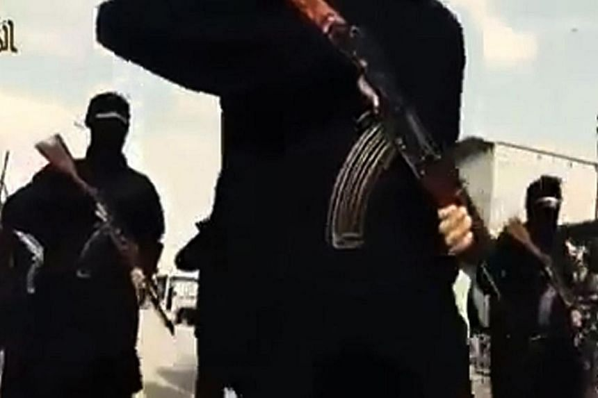 An image grab taken from a video released by the Islamic State in Iraq and Syria's (ISIS) official Al-Raqqa site via YouTube on Sept 23, 2014, allegedly shows Islamic State (IS) group recruits marching in an unknown location. The US has called for th