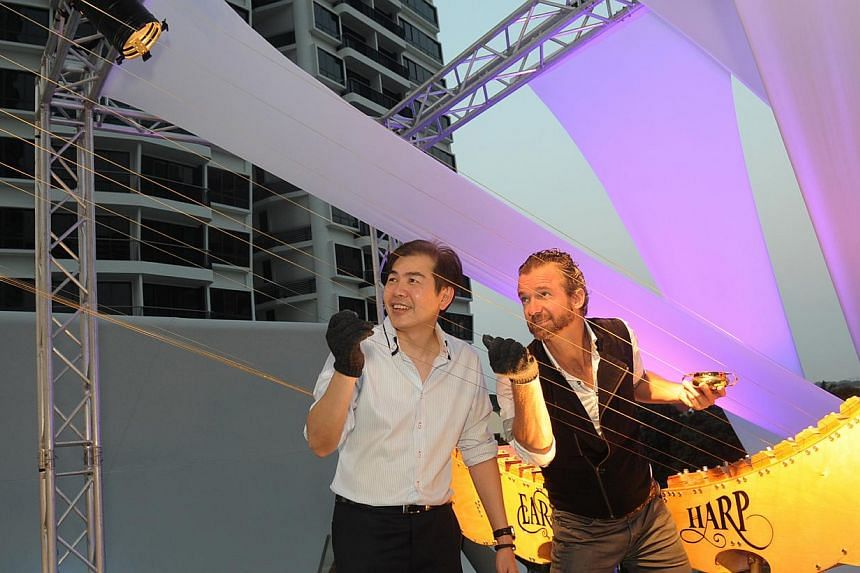 Mr Lim Ming Yan, president and group CEO of CapitaLand Ltd, tugged the strings of the Earth Harp with musician William Close at the celebration party of CapitaLand's d'Leedon. -- PHOTO: CAPITALAND