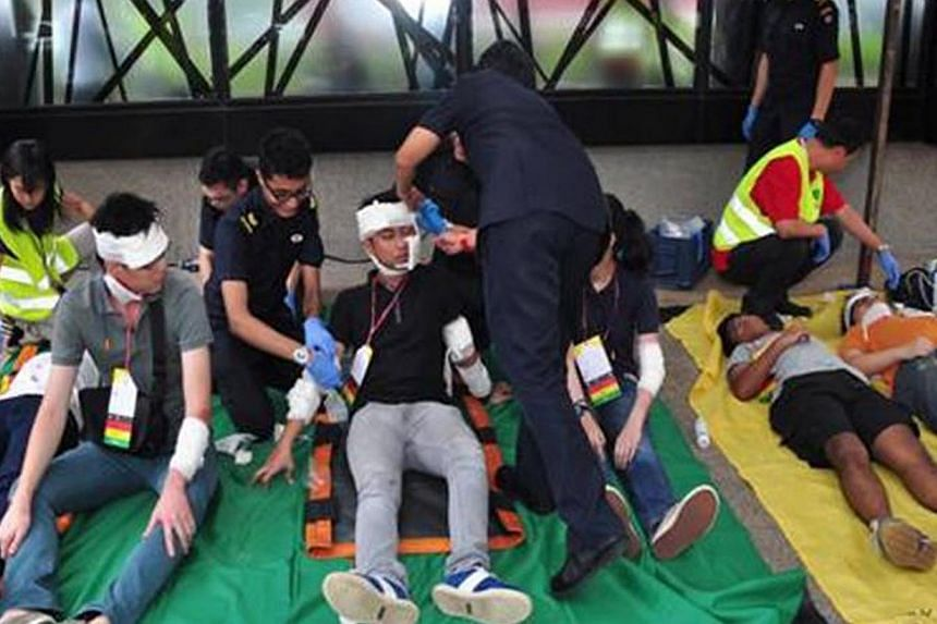 """Singapore Civil Defence Force personnel bandage """"casualties"""" on the second day of Exercise Heartbeat, an annual anti-terror exercise by the Singapore Police Force at the IMM Building.-- PHOTO: SINGAPORE POLICE FORCE"""