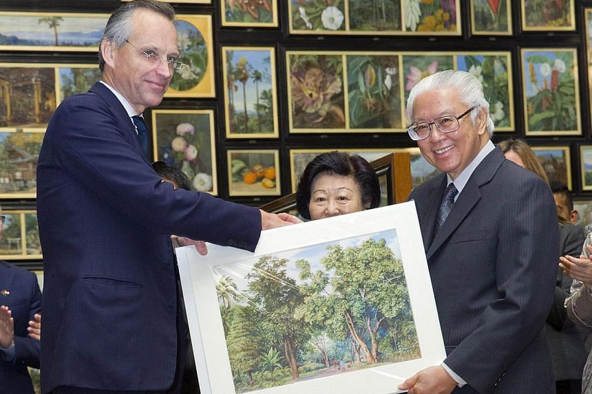 Singapore's President Tony Tan Keng Yam (right) receives a print of A Lane In Singapore as a gift from Lord de Mauley (left) in the Marianne North Gallery during a visit to Kew Gardens in West London on Oct 24, 2014. -- PHOTO: AFP