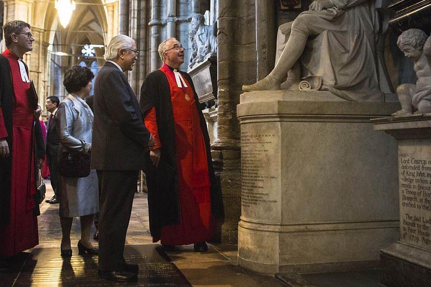 Singapore President Tony Tan Keng Yam and his wife Mary are shown the statue of Sir Thomas Stamford Raffles, the founder of Singapore, by Reverend Dr John Hall, Dean of Westminster in Westminster Abbey on Oct 21, 2014. -- PHOTO: AFP