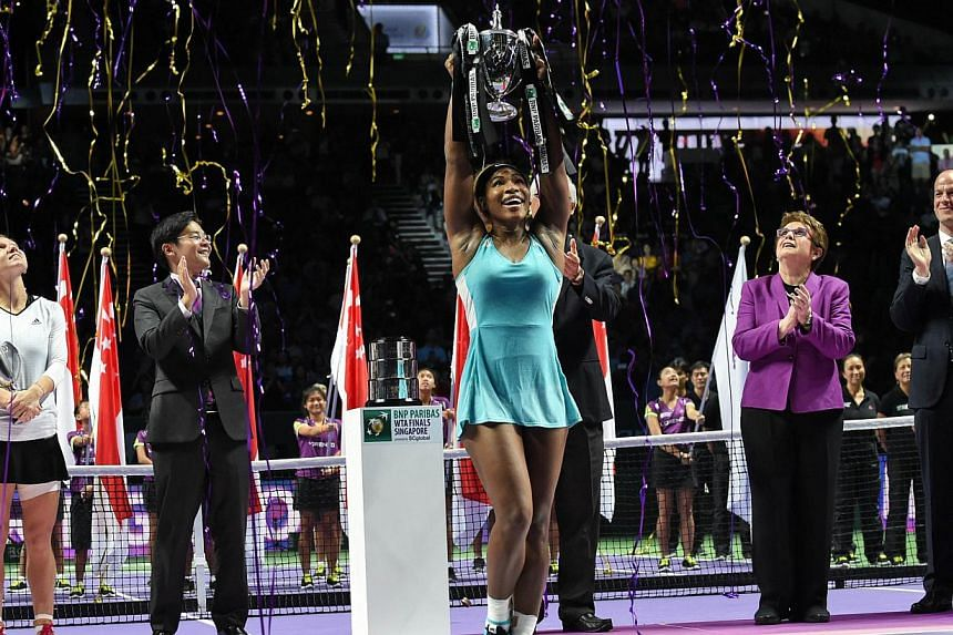 Serena Williams of the US (middle) lifts the trophy at the podium after defeating Simona Halep of Romania in the finals of the Women's Tennis Association (WTA) finals in Singapore on Oct 26, 2014. -- PHOTO: AFP