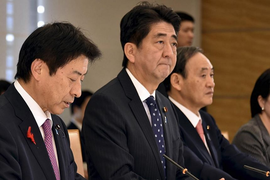 Japan's Prime Minister Shinzo Abe (second left), flanked by Labour, Health and Welfare Minister Yasuhisa Shiozaki (left), Chief Cabinet Secretary Yoshihide Suga (second right) and Internal Affairs and Communications Minister Sanae Takaichi (right), a