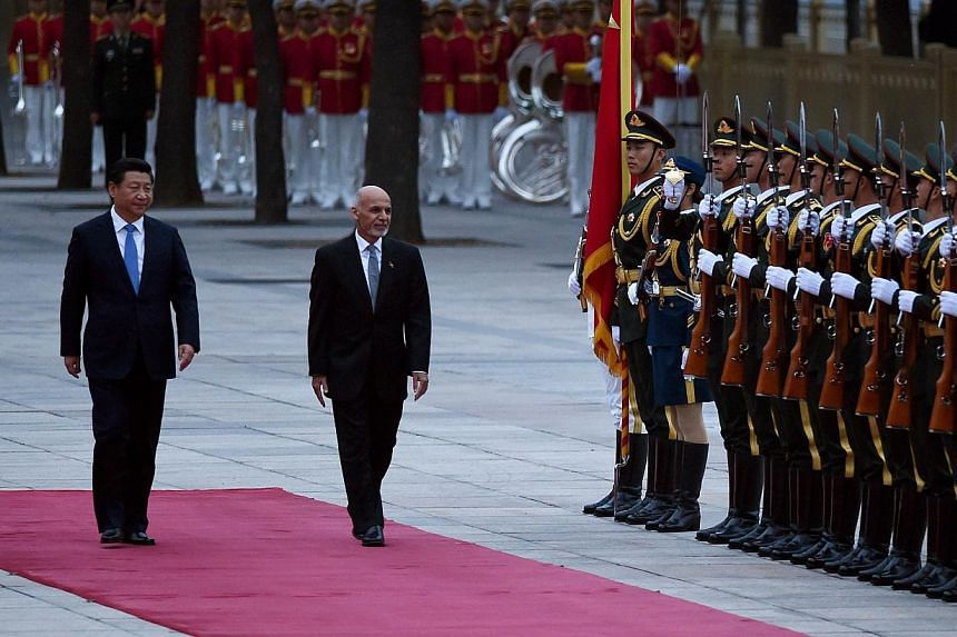 Afghanistan President Ashraf Ghani Ahmadzai (right) and Chinese President Xi Jinping (left) inspect Chinese honour guards during a welcome ceremony outside the Great Hall of the People in Beijing on Oct 28, 2014. -- PHOTO: AFP
