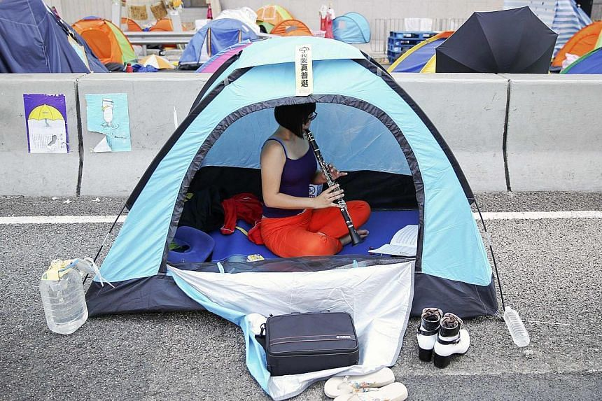An activist practices oboe in her tent set-up in a part of Hong Kong's financial central district occupied by pro-democracy protesters. -- PHOTO: REUTERS