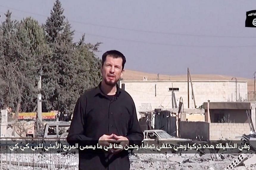 An image grab taken from a video released by the Islamic State (IS) group group via Youtube on Oct 27, 2014 purportedly shows 43-year-old kidnapped British reporter John Cantlie standing in a war-damaged town, talking to the camera and rejecting US c
