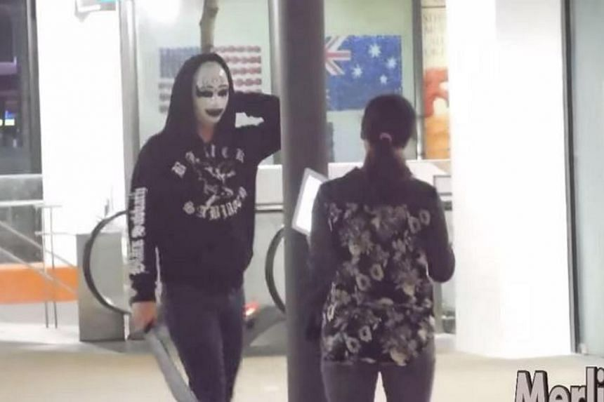 A screengrab from the Purge Prank video posted on YouTube by MerlionTV, which shows a masked man wielding a knife scaring a woman. -- PHOTO: SCREENGRAB FROM YOUTUBE