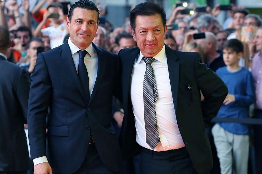 Valencia's new owner Peter Lim (right) and Valencia's President Amadeo Salvo pose during the Spanish league football match Valencia FC vs Elche CF at the Mestalla stadium in Valencia on Oct 25, 2014. -- PHOTO: AFP