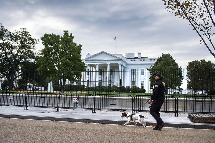 A US Secret Service Uniformed Division officer and his K-9 dog patrol the fence line of the White House in Washington, DC, on Oct 23, 2014. -- PHOTO: AFP